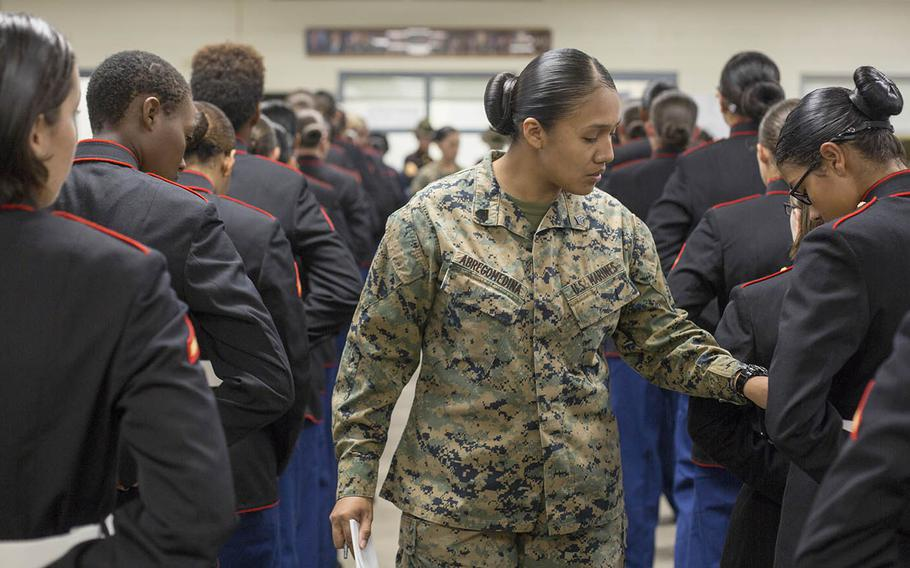 Sgt. Cristal Abregomedina, a warehouse clerk with Headquarters and Service Battalion, examines the uniforms of Marines from November Company, 4th Recruit Training Battalion at Marine Corps Recruit Depot Parris Island, S.C., Nov. 9, 2018.