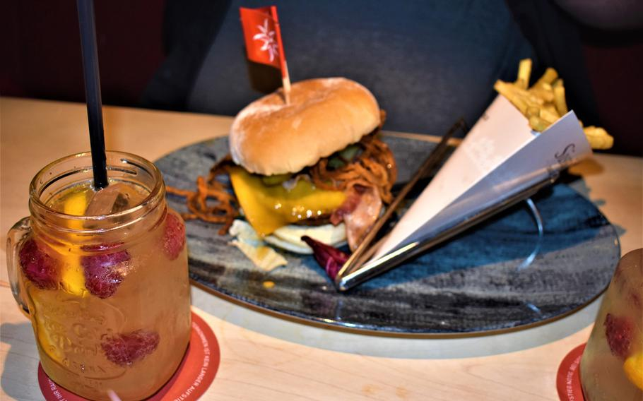 A bacon cheeseburger known as the Joseph is presented along with a side of fries and an Orange Berry detox water at Franz und Sissi restaurant in Kaiserslautern, Germany. The restaurant offers a lunch special adding fries and a specialty drink for 3.95 euros above a burger's menu price.
