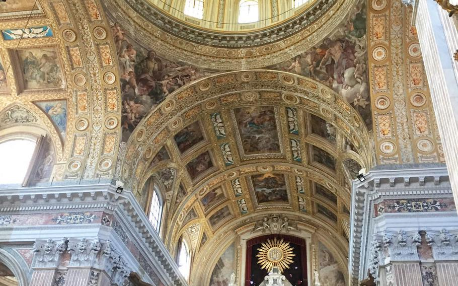 A gold dome is at the center of the vaulted ceilings covered with religious frescoes in the Church of Gesu Nuovo in Naples, Italy.