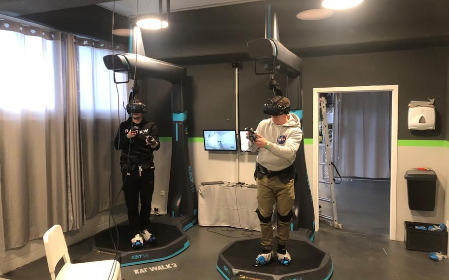 Customers at VArea in Mainz, Germany, use a Katwalk setup to fully immerse themselves in a virtual reality first person shooter game on Jan. 8. The gaming setup allows users to maneuver within the virtual reality environment without leaving the enclosed setup.