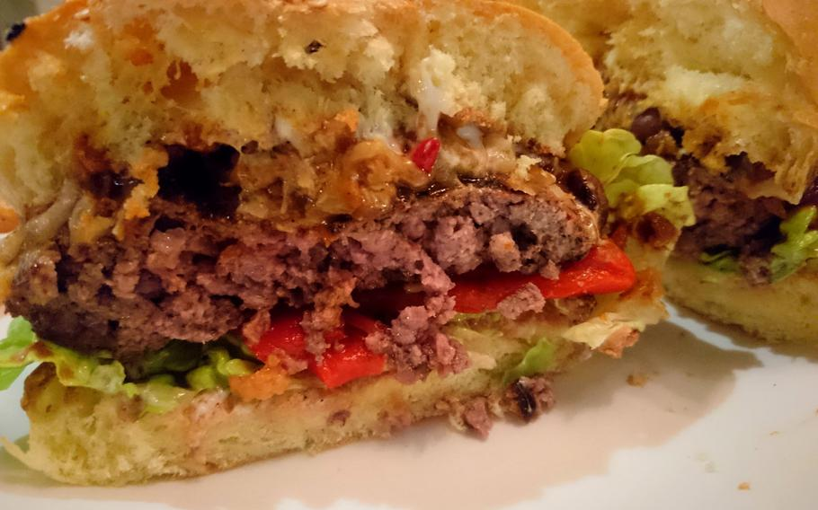 A bisected order of the weekly burger creation at Bill's Restaurant in Bury St Edmunds, England, Feb. 26. The black bean chili burger had melted white cheese slathered over grilled chopped onions, a thick beef patty, lettuce and mildly spicy red peppers.