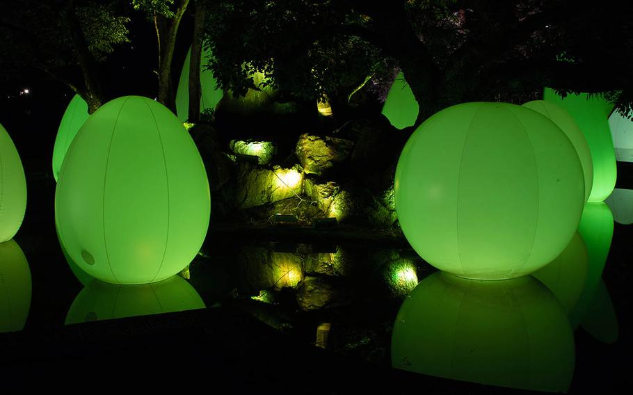 Colored eggs, or ovoids, reflect a brilliant green onto the surface of a small pool Feb. 27 near Hiroshima Castle, Japan.