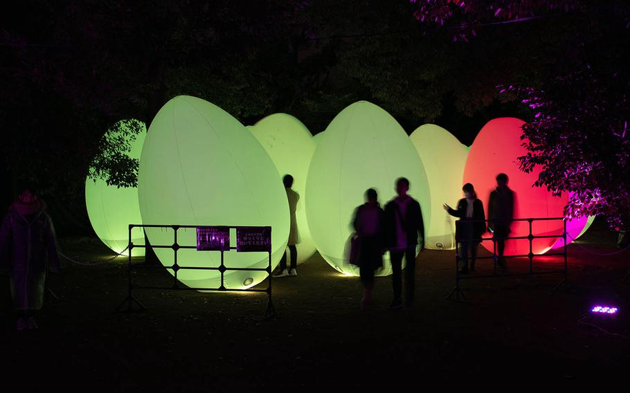 Visitors walk among giant colored eggs during an art exhibit Feb. 27 at Hiroshima Castle, Japan.