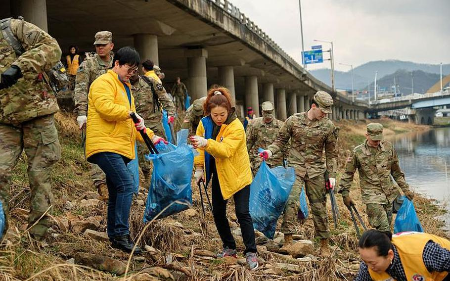 U.S. soldiers from Camp Casey and local volunteers clean up debris along the Shincheon River in Dongducheon, South Korea, Thursday, March 21, 2019.