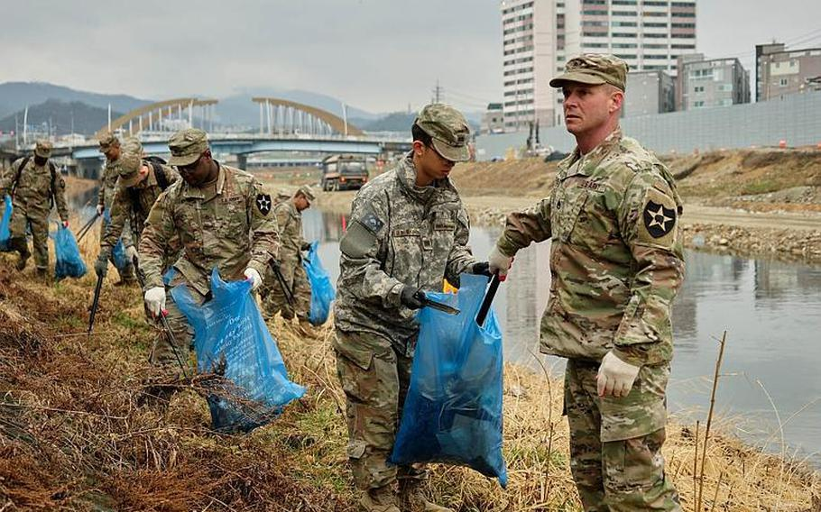 U.S. soldiers from Camp Casey clean up debris along the Shincheon River in Dongducheon, South Korea, Thursday, March 21, 2019.