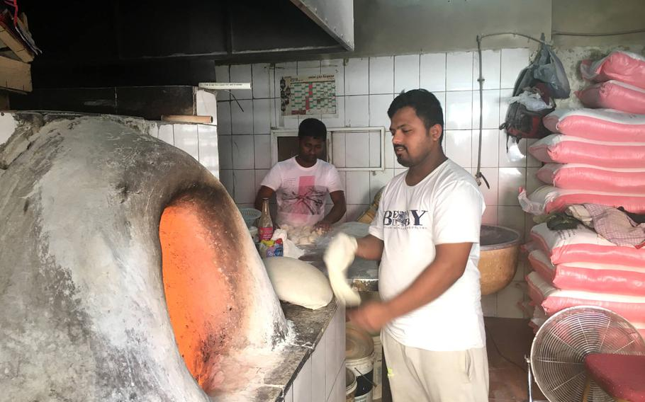 A baker cooks flatbread in a clay oven in Qudaibiya, Bahrain on March 29, 2019.