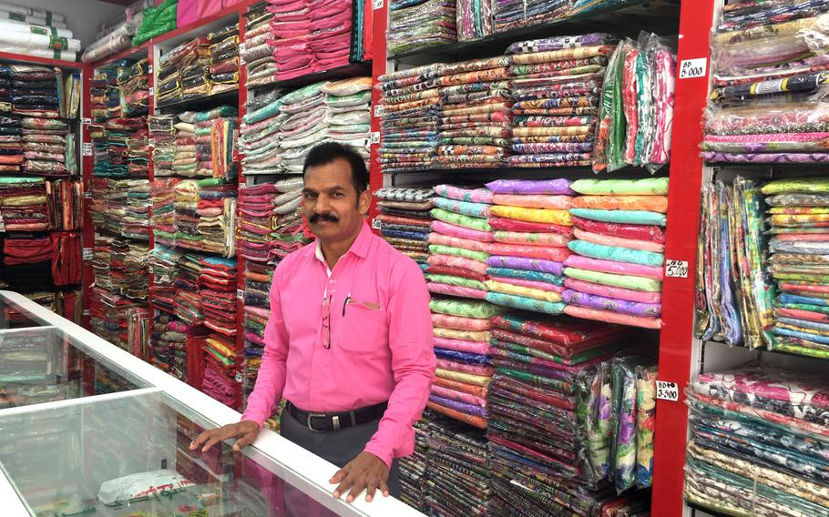 A shop owner poses for a photo inside his textile store in Qudaibiya, Bahrain.