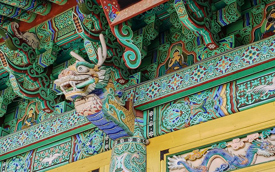 Upon arriving at the entrance of Mangisa Temple, visitors pass through a gate decorated with intricate wooden carvings of dragons.