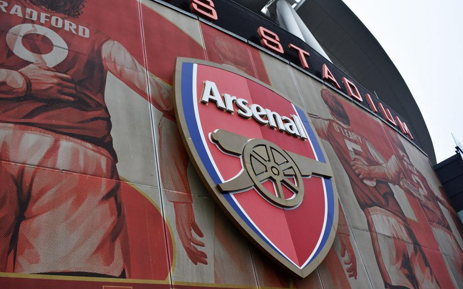 """The logo of the Arsenal soccer team and a mural of legendary Arsenal players adorn the outside of Emirates Stadium in London. The team's """"Arsenalization"""" project increased the amount of historic Arsenal imagery on the new, modern stadium."""