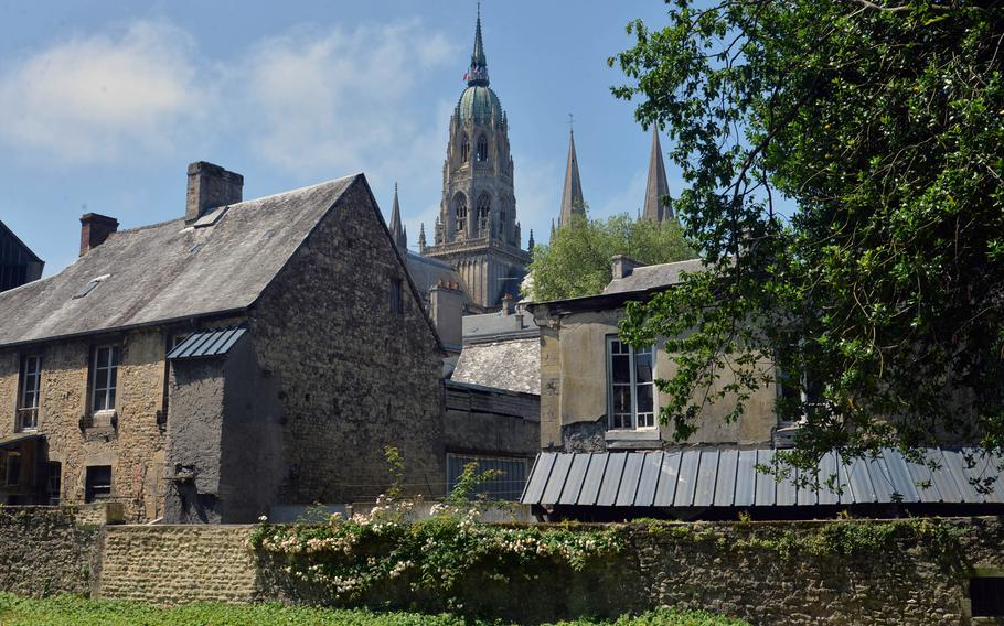 The 13th century Notre Dame Cathedral in Bayeux, France, towers over the streets of the city, as seen from a peaceful park.