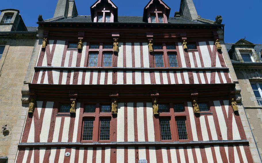 One of the old half-timbered houses in Bayeux historic city center. Note the carved figures adorning the house.