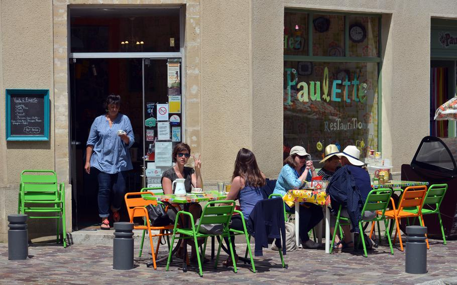 People enjoy something to drink at a cafe with colorful tables and chairs in old town Bayeux, France.