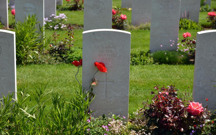 A pair of poppies lean against the gravestone of an unknown soldier at Bayeux War Cemetery. It is the largest Commonwealth cemetery in Normandy, with 4,848 soldiers from the United Kingdom and other countries buried here.