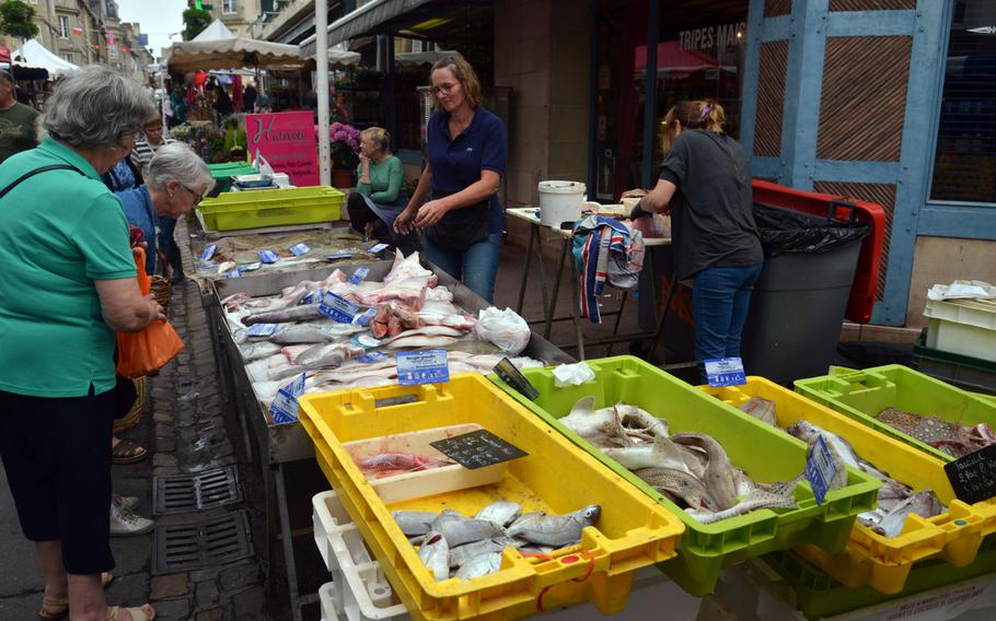 Shoppers stop to inspect the fish on sale at a stand at the Wednesday morning market on Rue Saint Jean in Bayeux, France.