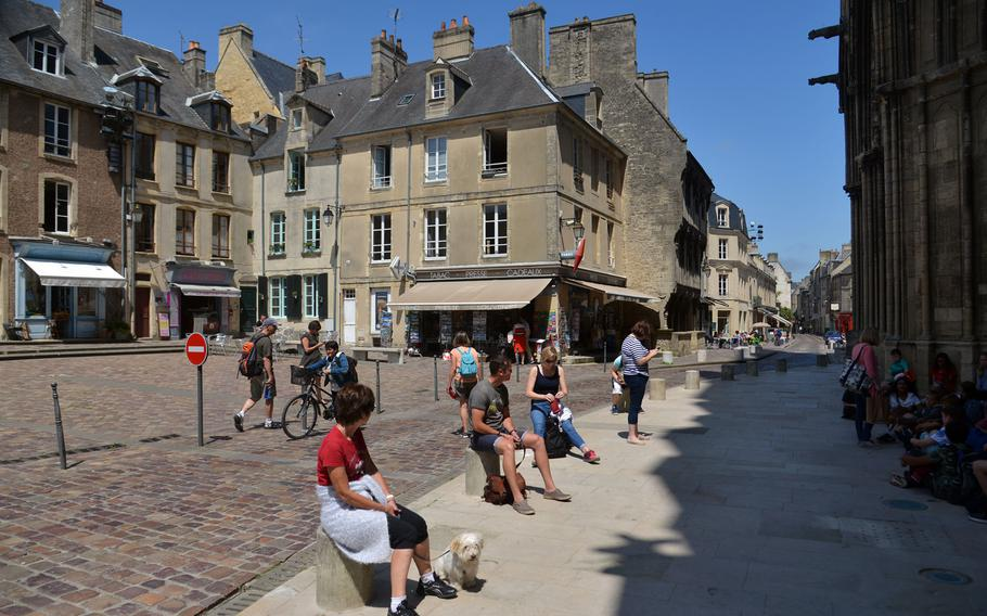Visitors sit on a shop-lined Bayeux square, in front of the cathedral.