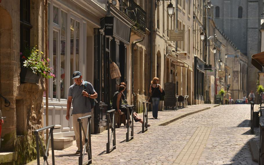 People walk up the cobblestoned Rue des Cuisiniers in the old Normandy city of Bayeux, as a pair of shopkeepers have a conversation.