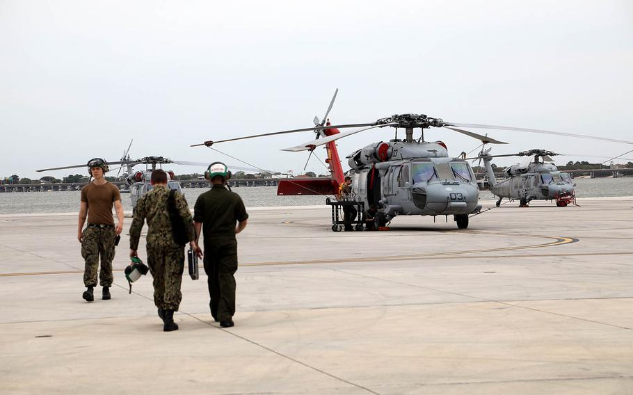 """Sailors walk on the flight line near MH-60S Knighthawk helicopters with the Helicopter Sea Combat Squadron two, the """"Fleet Angels,"""" at Naval Station Norfolk in Virginia on April 26, 2019."""