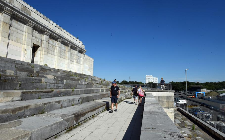 Tourists walk around the viewing stands of the Nazi Party Rally Grounds in Nuremberg, Germany. One tourist stands in Hitler's area near the ledge.