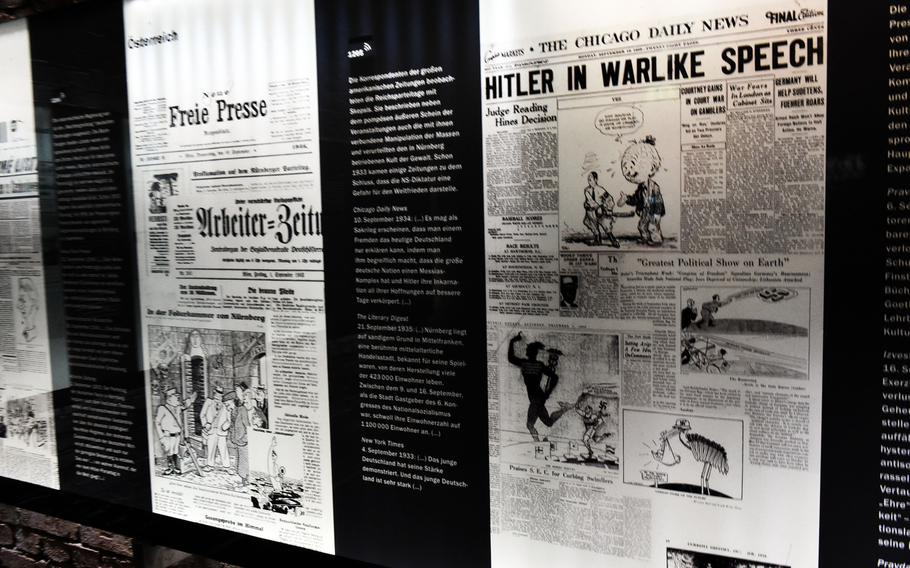 """An exhibit inside the museum of the Documentation Center Nazi Party Rallying Grounds, in Nuremberg, Germany, showing newspapers from around the world reacting to the Nazi movement in Germany. One Headline reads, """"Greatest Political Show on Earth"""", while others condemn Hitler's warlike speech."""