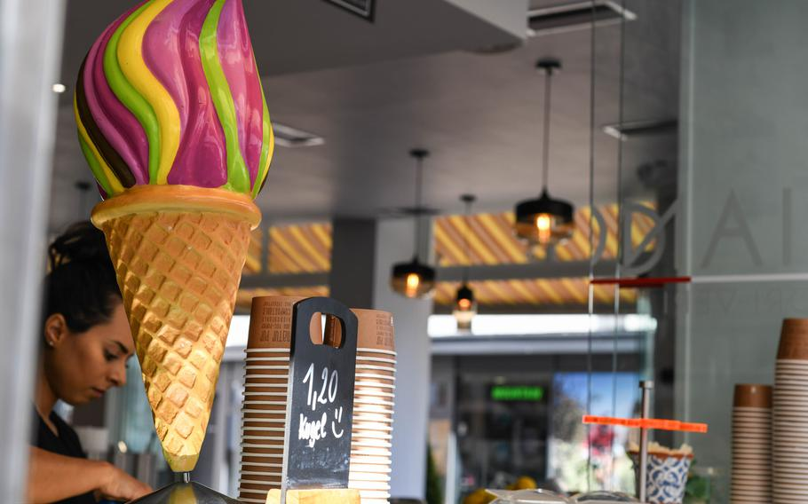 A server works behind a large plastic ice cream cone at Italiano Sapori Veri in Kaiserslautern, Germany, on July 23. Sapori Veri sells 18 flavors of homemade ice cream from a window adjacent to its sit-down restaurant and cafe.