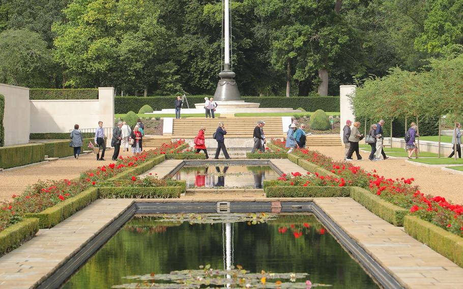 Visitors with a tour walk past the reflection pool on the Cambridge American Cemetery grounds.