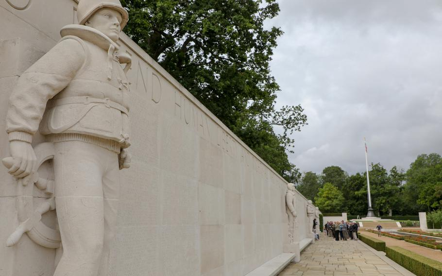 Visitors listen to a tour guide at the Wall of the Missing on Aug. 12, 2019, on the Cambridge American Cemetery grounds.