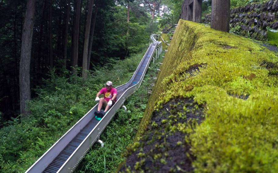 A rider picks up speed as he hits the steeper parts of Japan's longest roller slide in the village of Tabayama.