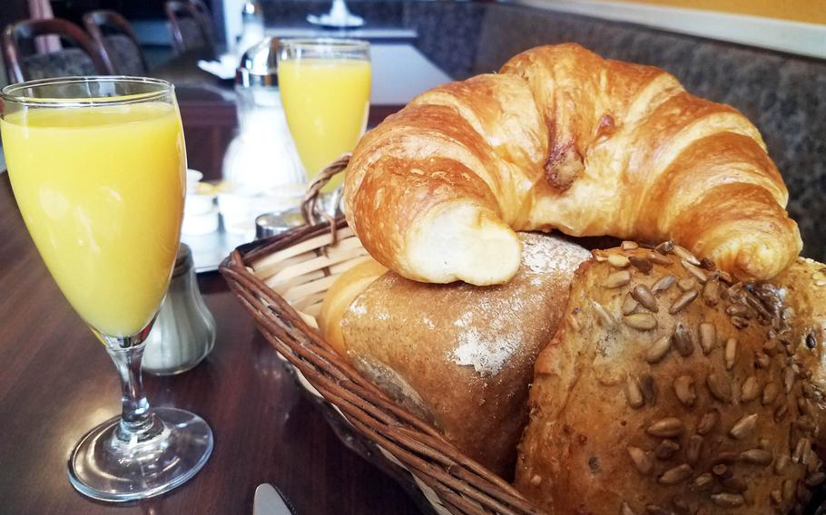 A stack of rolls and croissants and two glasses of orange juice at Backerei Konditorei Cafe Bauer, in Grafenwoehr, Germany.