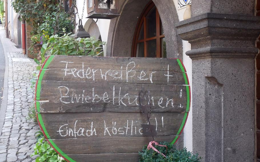 A sign in front of a wine tavern in Cochem, Germany, announces it offers Federweisser and Zwiebelkuchen. The former is a partially fermented young wine, while the latter is an onion tart. They are traditionally served in the autumn during the grape harvest season.