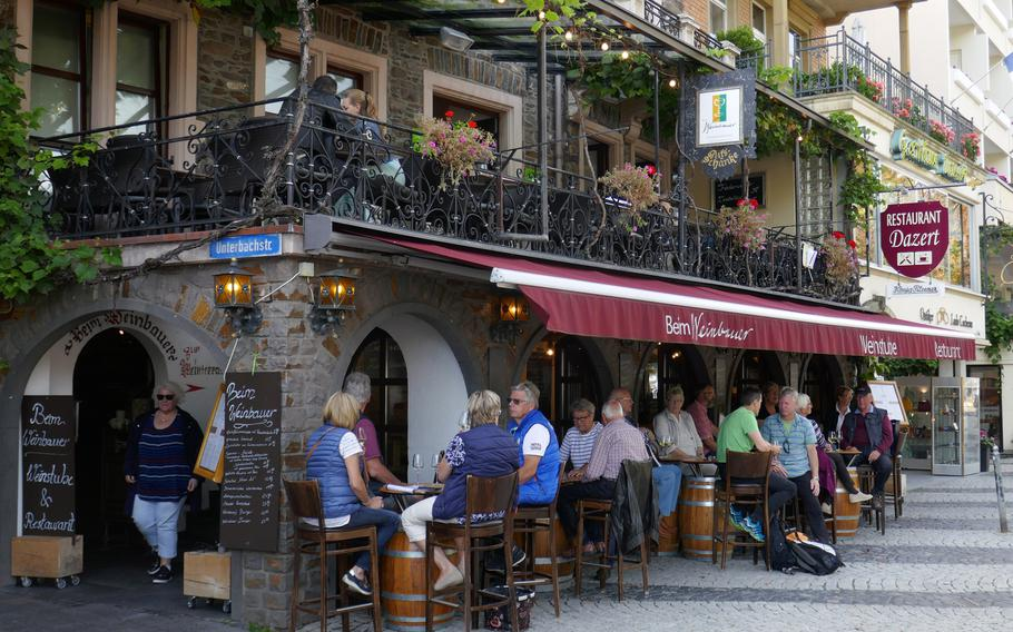 Visitors to Cochem, Germany, taste the wine at wine tavern near the Moselle River.