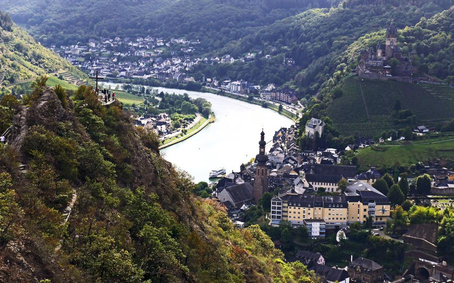 A view of Cochem, Germany, from the chairlift station above the city. At left, people have a look from the viewing platform at the Pinner Cross, the Reichsburg towers over Cochem at right.