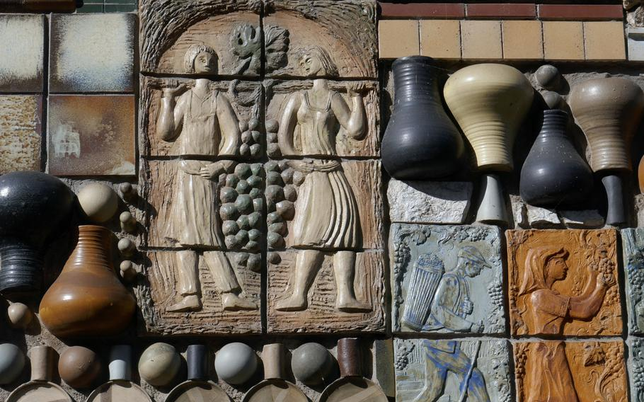 Cochem, on the Moselle River, is famous for its wine and vineyards. Here tiles on a house has many grape harvest motifs.