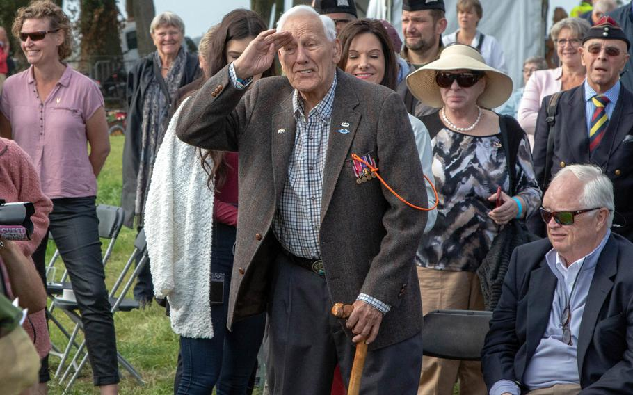 Gene Metcalfe, a World War II veteran and former POW, salutes the crowd after being awarded the Military Order of William in Groesbeek, Netherlands, Sept. 18, 2019. Sitting at right is Richard Blankenship who accepted the award on behalf of his late father, Robert C. Blankenship.