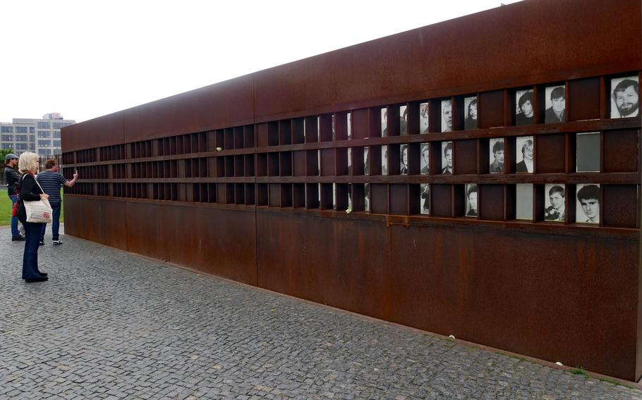Visitors look at the photos that make up the Window of Remembrance at the Berlin Wall Memorial. The monument is dedicated to the 136 people who lost their lives at the Wall.