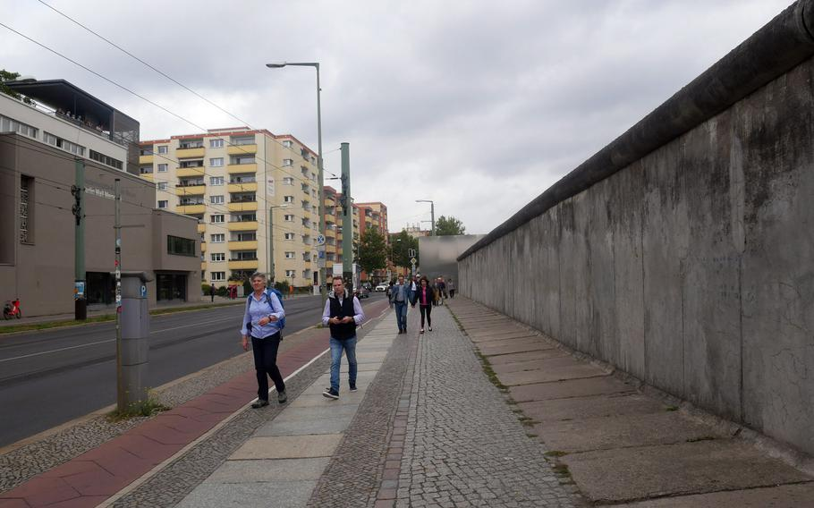 Tourists walk along the remnants of the Berlin Wall on Bernauerstrasse. They would be walking in West Berlin if this was Nov. 8, 1989.
