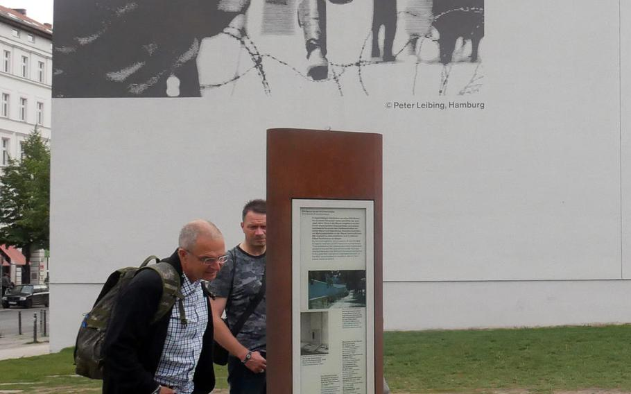 Visitors check out an information table at the Berlin Wall Memorial Complex on Bernauer Strasse. On the wall behind them is one of the most famous photos from the early days of the Wall's construction, an East German border guard jumping over the barbed wire to freedom.