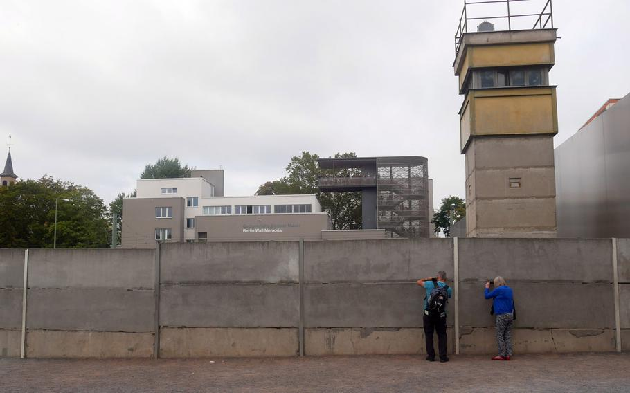Visitors photograph through cracks in the wall at the Berlin Wall Memorial. This wall would have been one of the first barriers an escapee to the West would have to cross, lower than the infamous one directly on the border. In the background is the memorial's Documentation Center viewing platform.