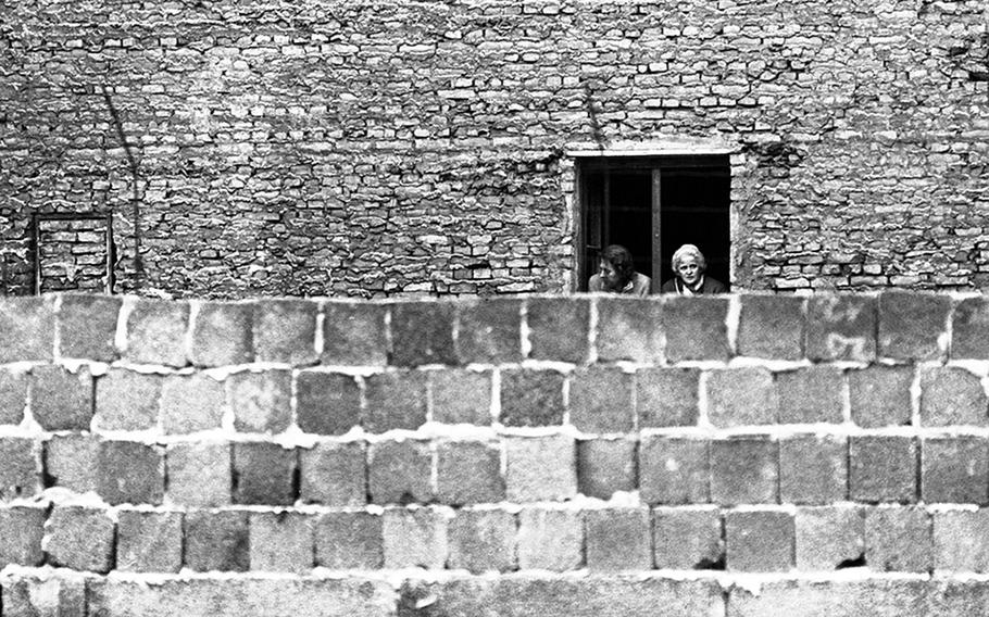 Two East Berliners look out their window onto a newly-strengthened section of the first-generation Berlin Wall at Bernauerstrasse in October 1961. Later the houses along the East Berlin side of the Wall were demolished.