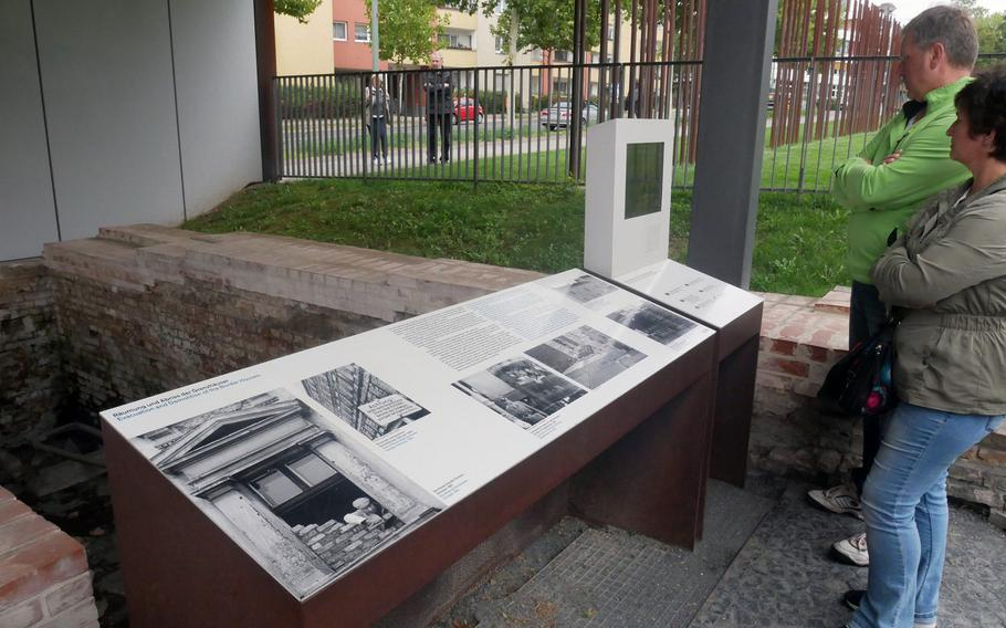 Visitors to the Berlin Wall Memorial complex on Bernauer Strasse read an information table on the evacuation and destruction of houses along the Berlin Wall. The foundations of one of them can be seen behind the table.