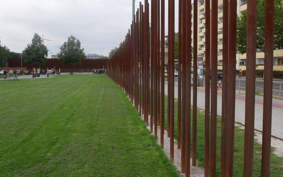 Rusted metal poles mark where the Berlin Wall once stood along Bernauer Strasse. They are part of the Berlin Wall Monument complex. The view would be from East Berlin looking to the west.