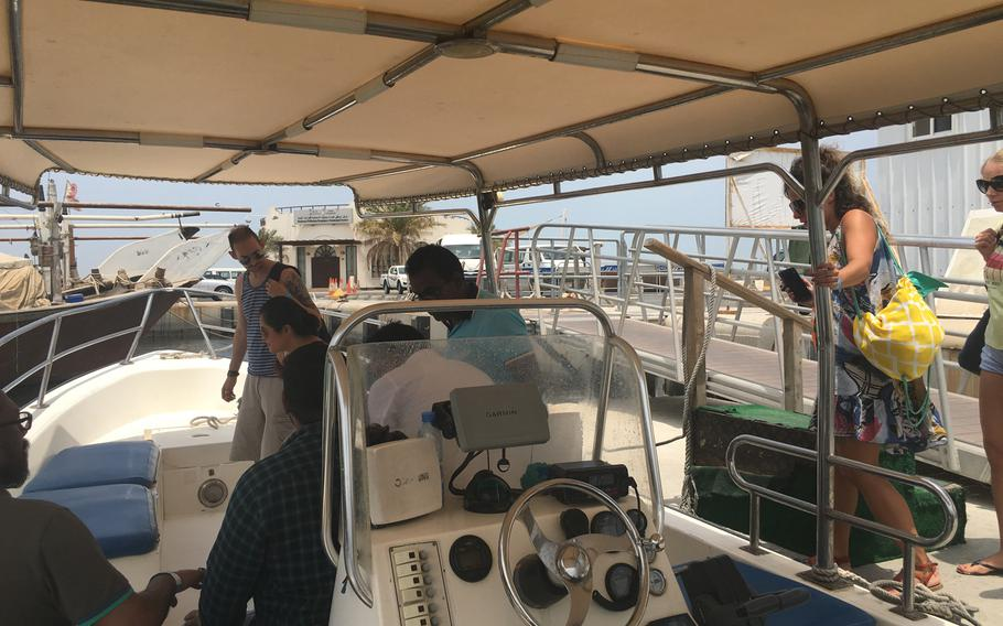 Visitors board a transit boat at Sitra Fisherman Port on their way to Al Dar Island, Aug. 12, 2019.