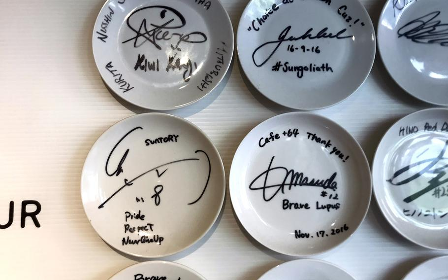 A wall at the+64 Cafe in western Tokyo is decorated with saucers signed by professional rugby players.