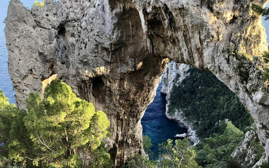 View from behind Arco Naturale, a rock formation on Capri's southern cliffs, overlooking the Mediterranean Sea.