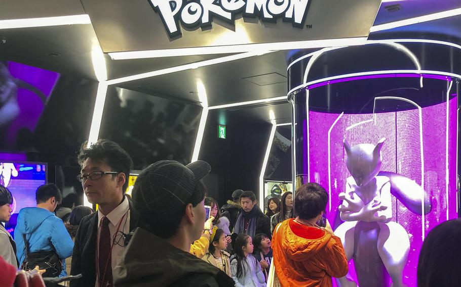 Customers take photos of a Mewtwo statue while waiting to enter the Pokemon Center near Nintendo Tokyo in Shibuya, Sunday, Dec. 1, 2019.