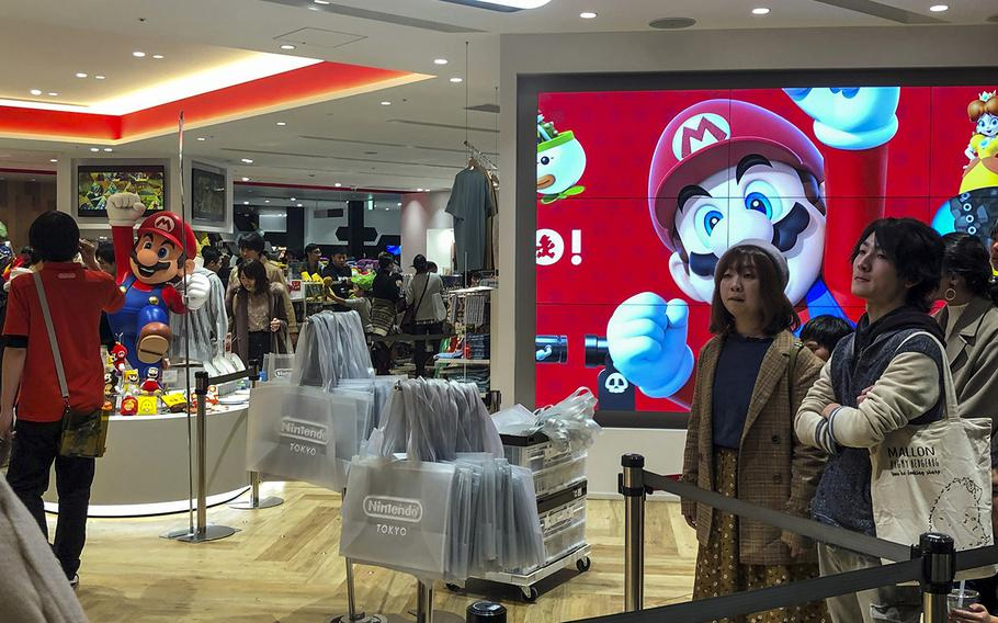 Customers wait to enter Nintendo Tokyo on the sixth floor of the Parco Shibuya department store in Tokyo, Sunday, Dec. 1, 2019.