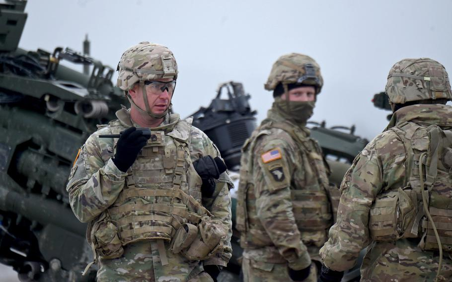 Sgt. 1st Class Rocky Johnson, left, communicates with a command center before the 2nd Cavalry Regiment conducts a live-fire exercise in Vilseck, Germany, Dec. 12, 2019.
