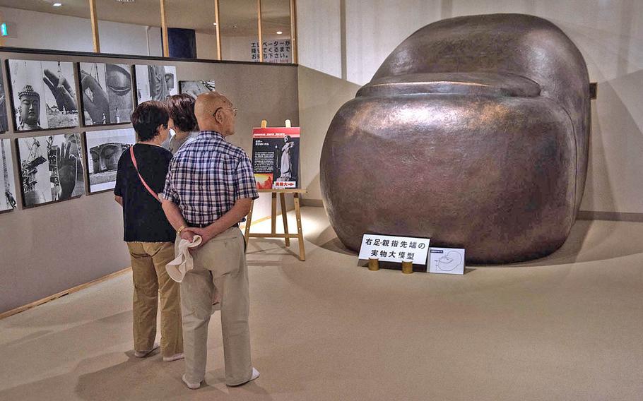 Tourists walk through the interior of the Ushiku Daibutsu, viewing photographs, sculptures and a replica of its toe, Sept. 18, 2019.