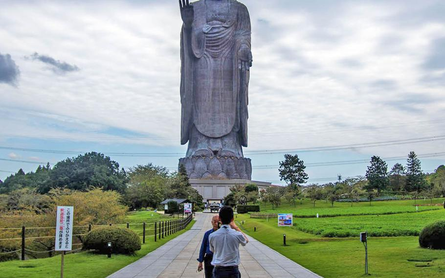 Tourists pose in front of Japan???s tallest bronze Buddha statue in Ibaraki prefecture, Sept.18, 2019.