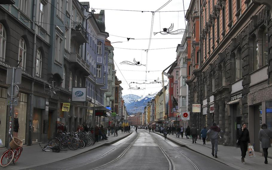 A street view of Innsbruck's colorful city center. No matter which way you look, you will see mountains in the distance as the city is surrounded by the Alps.