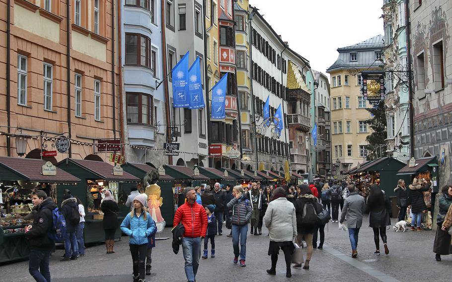 Innsbruck's bustling city center with Christmas markets in full swing. The colorful city is located in a valley that's completely surrounded by the Alps.